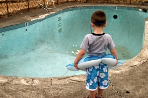 boy-looking-at-empty-swimming-pool