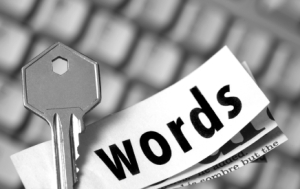 "black and white picture of a key with a piece of paper with ""words"" written on it; keywords concept"