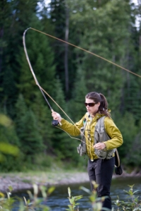 picture of a woman on a rive casting a fly-fishing rod