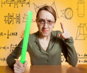 crazy female teacher sitting in front of a black board with a  ruler and critical look on her face