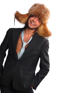 young man in a fur hat wearing a sloppy tie and jacket with no shirt