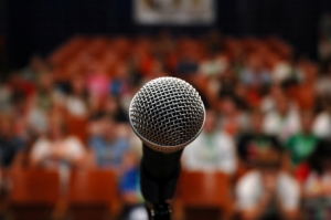 close up of microphone with an audience in the background