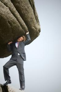 business man pushing a huge boulder up on his shoulder