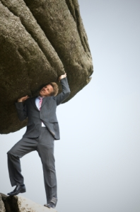 business man pushing a huge boulder up on his shoulder