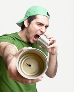 Guy yelling into one end of a tin can phone