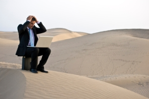 A businessman in a suit with his laptop is desperate in the desert