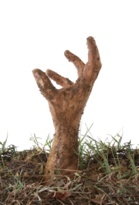 a zombie hand comes out of the grave