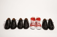 concept of unique style: red sneakers stand out alongside a row of black business shoes.